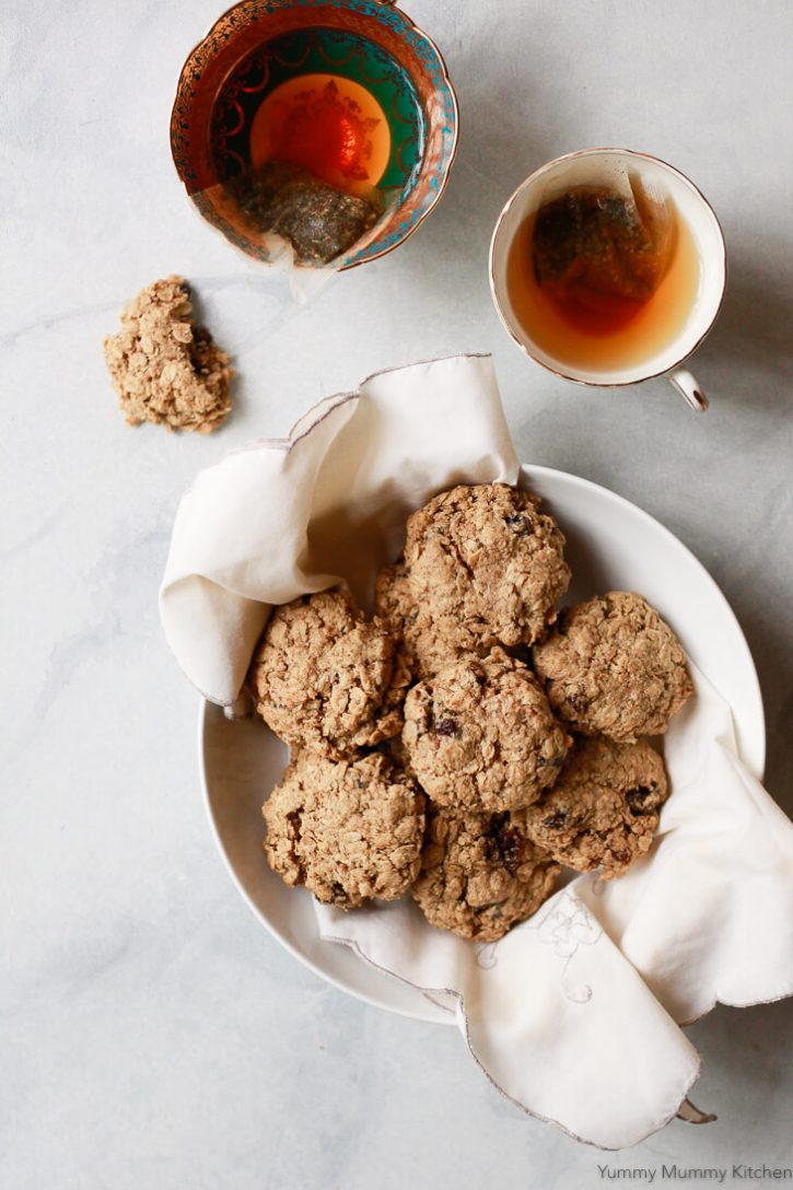 A white bowl filled with classic chewy oatmeal raisin cookies on a marble counter with two cups of tea.