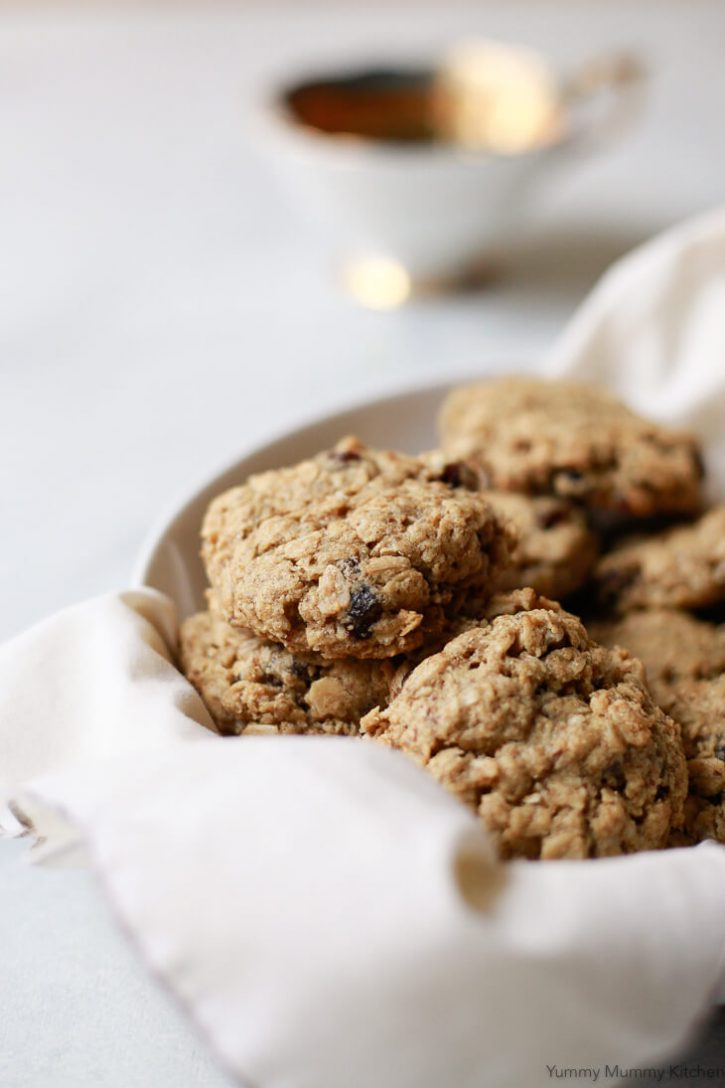 Close up photo of classic chewy oatmeal raisin cookies in a white bowl. These delicious oatmeal raisin cookies are vegan and gluten free.