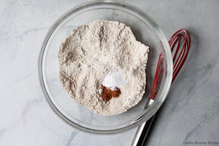 Oat flour, baking soda, and cinnamon in a bowl to make gluten free oatmeal raisin cookies.