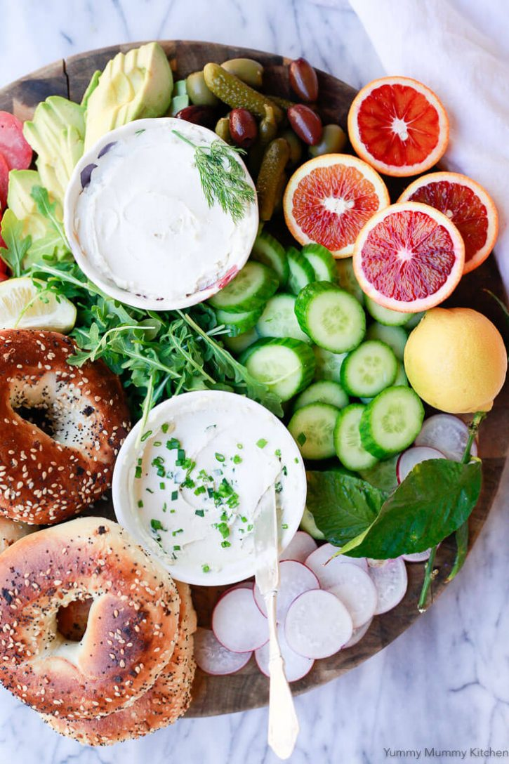 A beautiful breakfast bagel platter with two bowls of homemade vegan cream cheese with chives, cucumber, blood oranges, radish, avocado and olives on a round cutting board.