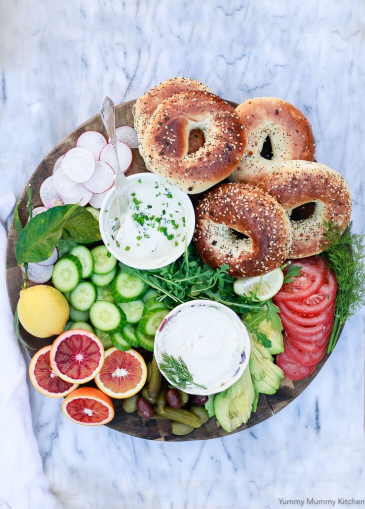 A colorful healthy breakfast or brunch platter with bagels, vegan cream cheese, fruits and vegetables.