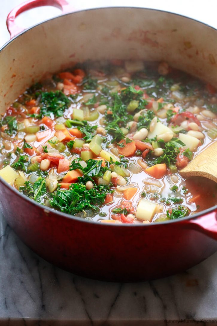 Hot steaming white bean and kale soup in a Dutch oven.