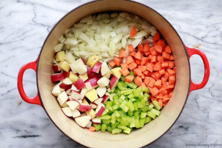 Chopped onions, carrots, celery, and potatoes in a Dutch oven to start a vegetable soup.