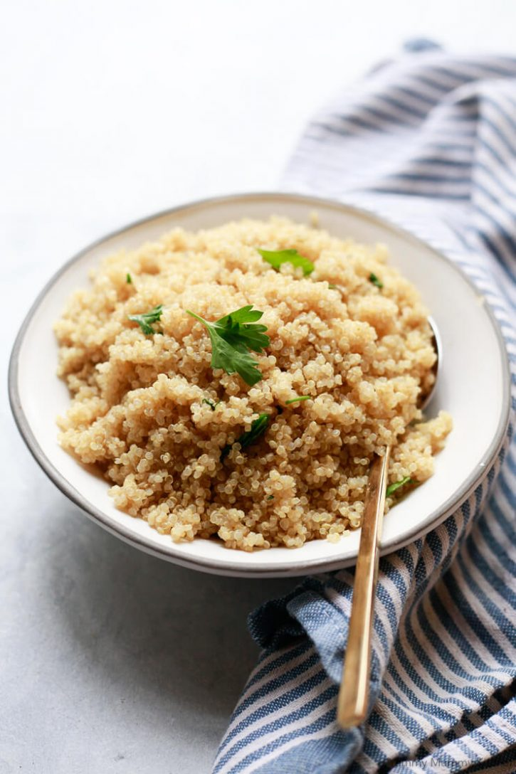 A white bowl filled with cooked fluffy white quinoa topped with parsley.