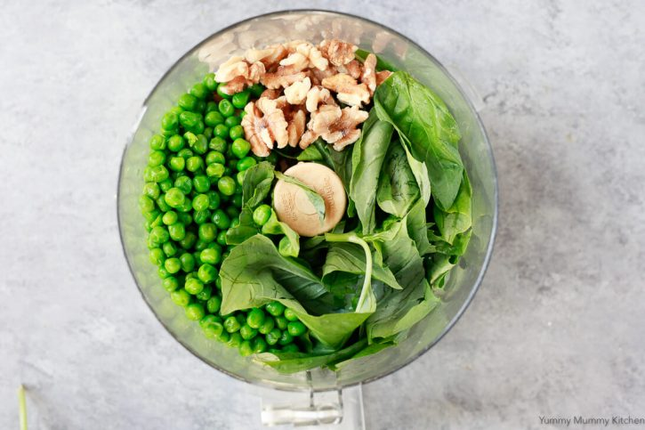 Ingredients for pea pesto in a food processor include walnuts, basil, and peas.