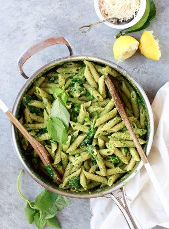 A pot filled with bright green pea and basil vegan pesto pasta.
