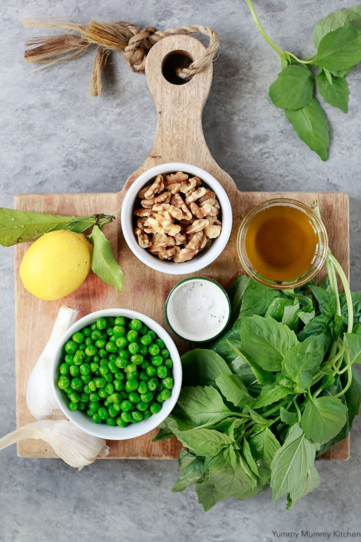 Ingredients for vegan pea and basil pesto on a wooden cutting board: whole lemon, bowl of walnuts, bowl of peas, fresh basil, garlic, salt, and olive oil.