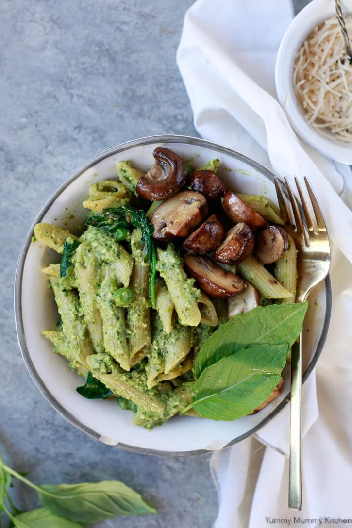 Pea pesto penne pasta in a white bowl with mushrooms and fresh basil. This vegan pesto pasta is a delicious lunch or dinner recipe.