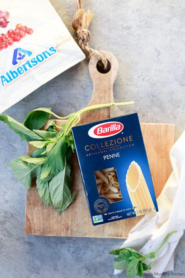 Barilla Collezione penne pasta on a cutting board with basil.