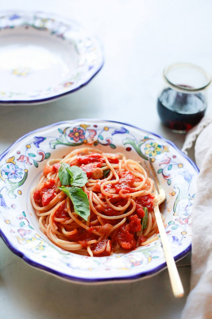 An Italian pottery bowl filled with spaghetti with pomodoro sauce and fresh basil.