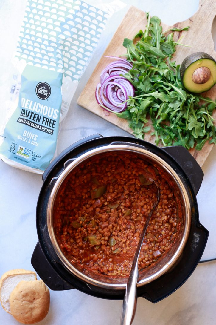 Vegan lentil sloppy joes in an Instant Pot pressure cooker with toppings on a cutting board including avocado, arugula, and red onion.