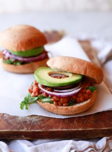 Vegan lentil sloppy joes on hamburger buns with onions and avocado.