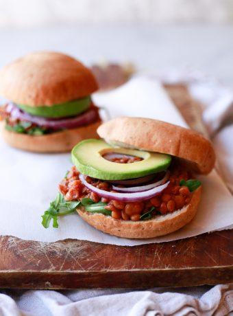 Vegan lentil sloppy joes on hamburger buns with onions and avocado.