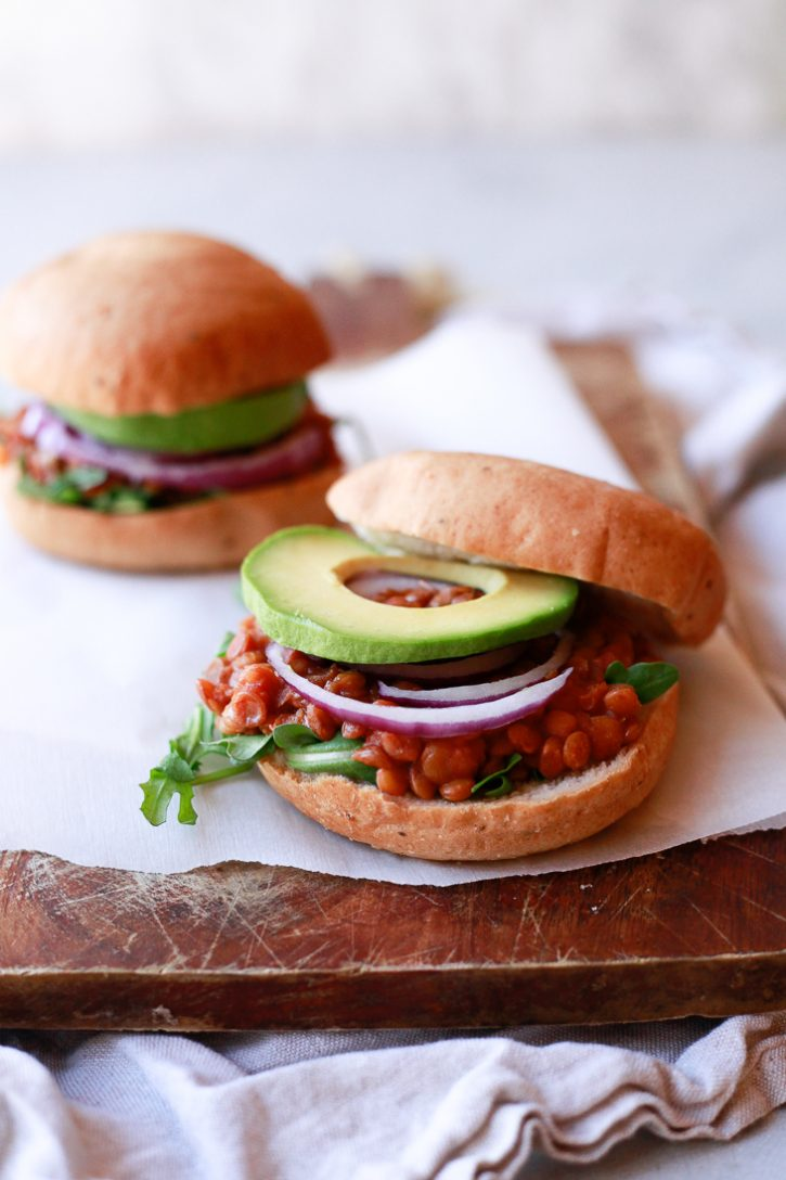 Vegan lentil sloppy joes on hamburger buns with onions and avocado rings.