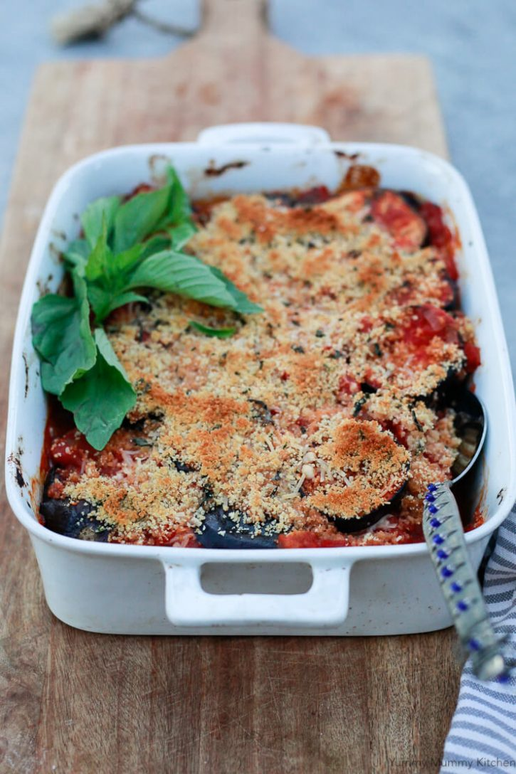 A white casserole dish with filled with baked vegan eggplant parmesan topped with golden brown breadcrumbs and garnished with fresh basil.