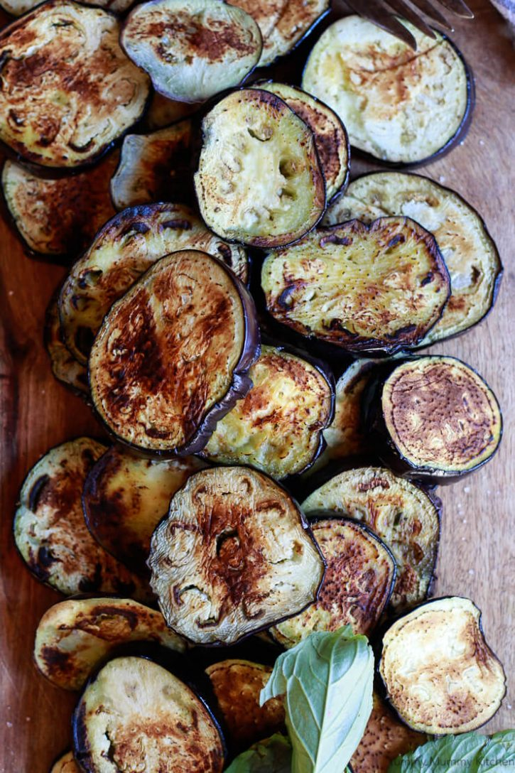 Beautiful browned eggplant slices sit on a cutting board ready to be assembled into a healthy vegan baked eggplant parmesan.