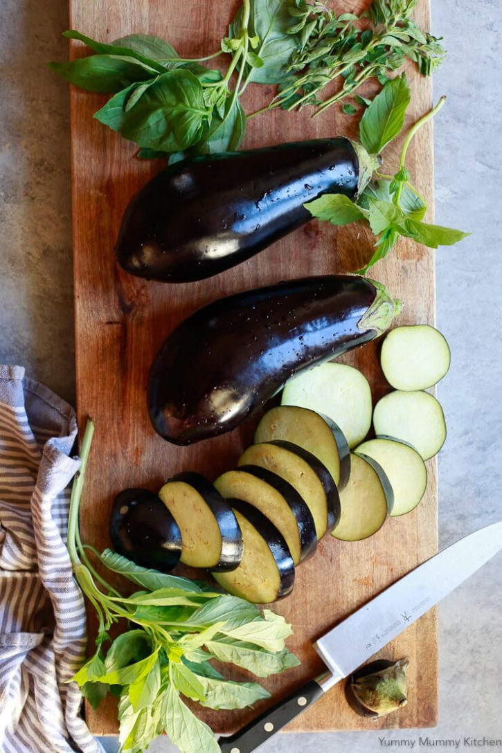 Eggplants are sliced on a wooden cutting board with basil.