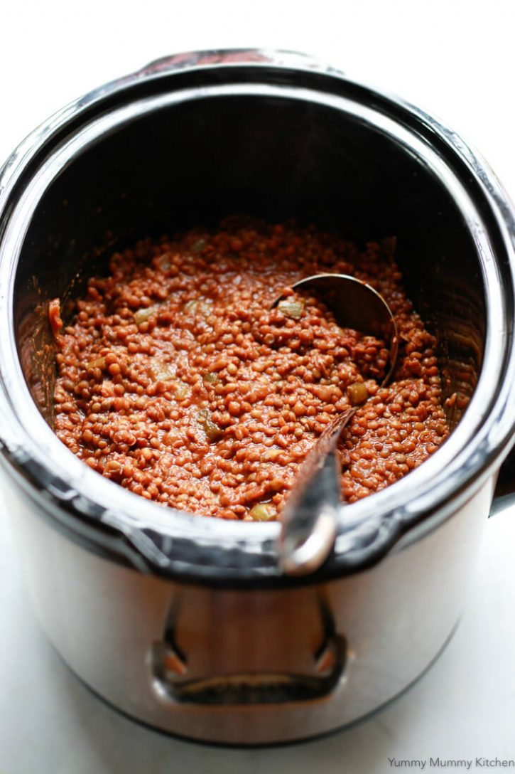 Vegan lentil sloppy joes in the slow cooker with a ladle.