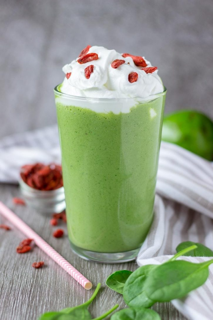 Green matcha smoothie topped with whipped cream and goji berries in a tall glass.