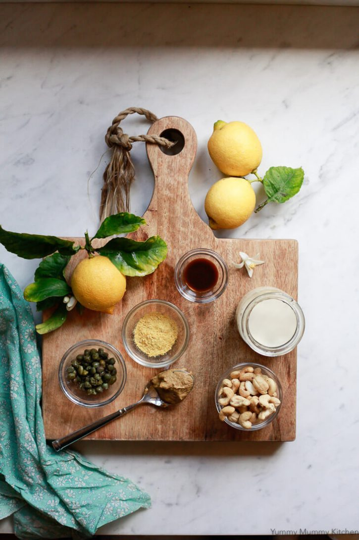 Ingredients for vegan Caesar salad dressing sit on a wooden cutting board in small bowls. Soaked cashews, almond milk, Worcestershire sauce, lemon juice, nutritional yeast, and capers.