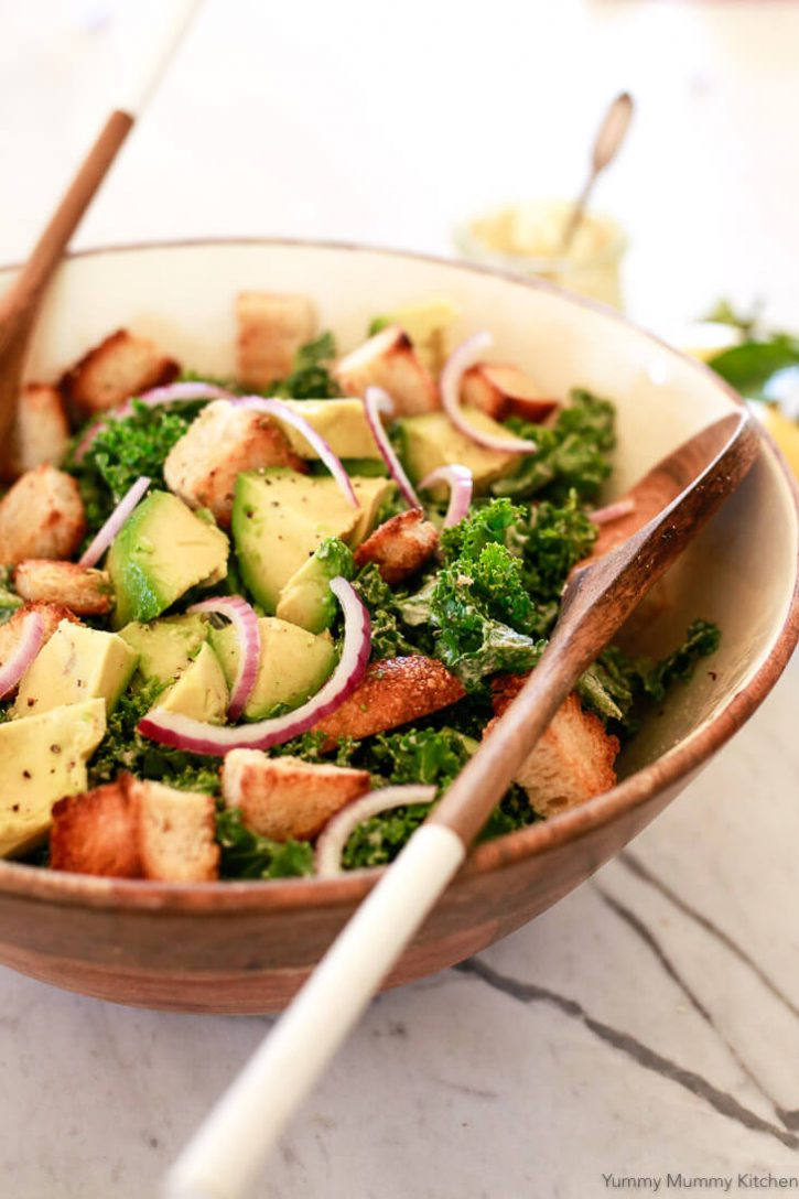 A big wooden bowl filled with vegan kale Caesar salad, croutons, avocado, and red onion slices.