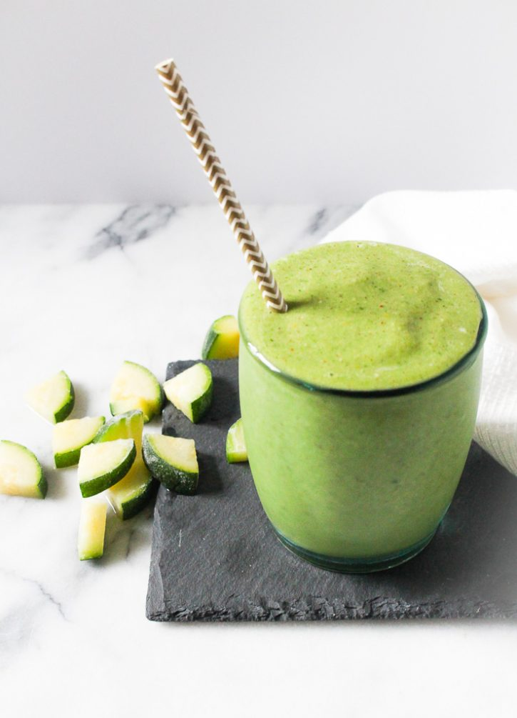 Green smoothie with a straw and chopped zucchini in the background.