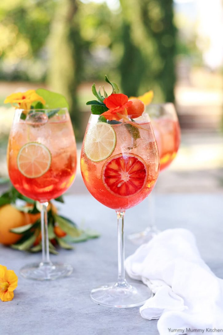 3 wine glasses filled with Aperol Spritz cocktail with blood oranges, limes, and edible flowers sit on a patio table.