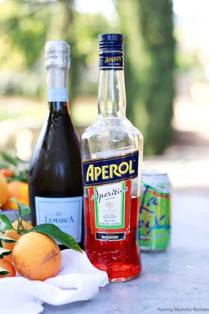 A bottle of Aperol with a bottle of prosecco in the background and fresh oranges on a table.