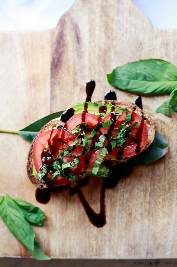 Delicious Italian Caprese avocado toast with tomatoes, basil, and a balsamic drizzle.