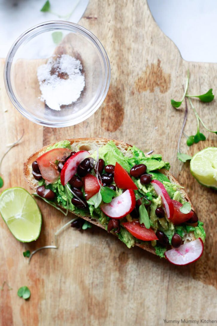 Southwest Mexican inspired Avocado Toast with black beans, lime, tomato, radish, and microgreens.