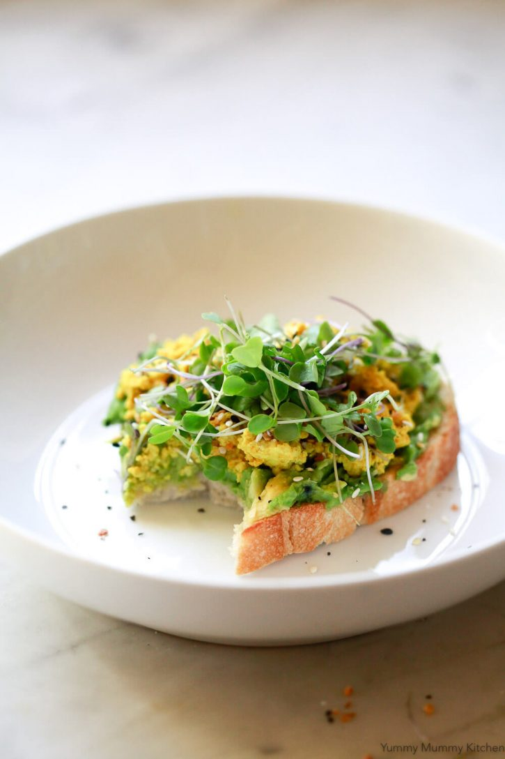 A piece of avocado toast with tofu scramble and microgreens.