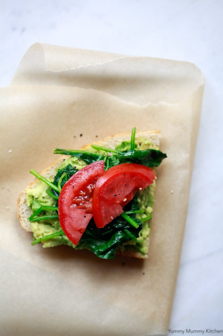 Half a slice of sourdough avocado toast with sauteed spinach and tomato slices. Healthy avocado toast recipe.