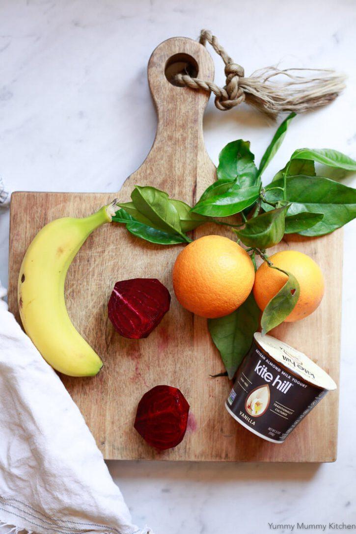 A raw beet, banana, oranges, vegan yogurt sit on a cutting board.