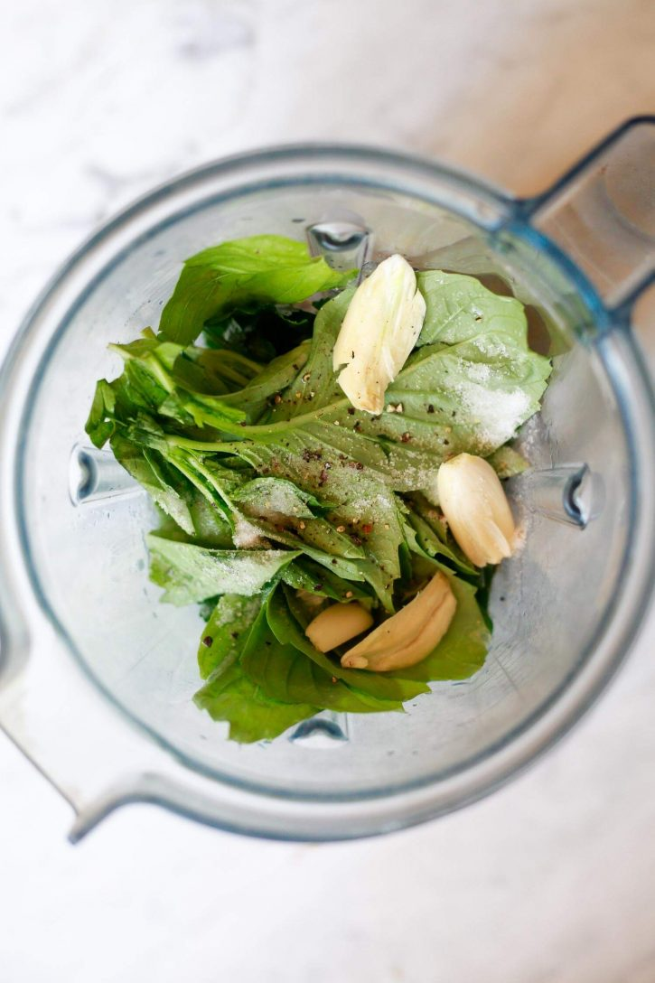 Fresh spinach, garlic, and other ingredients for avocado green goddess dressing in a Vitamix blender.