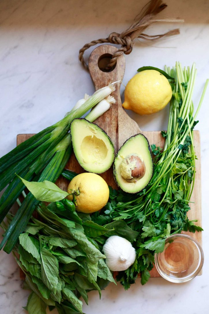Ingredients for vegan avocado green goddess dressing on a countertop include: avocado, lemon, herbs, and apple cider vinegar.