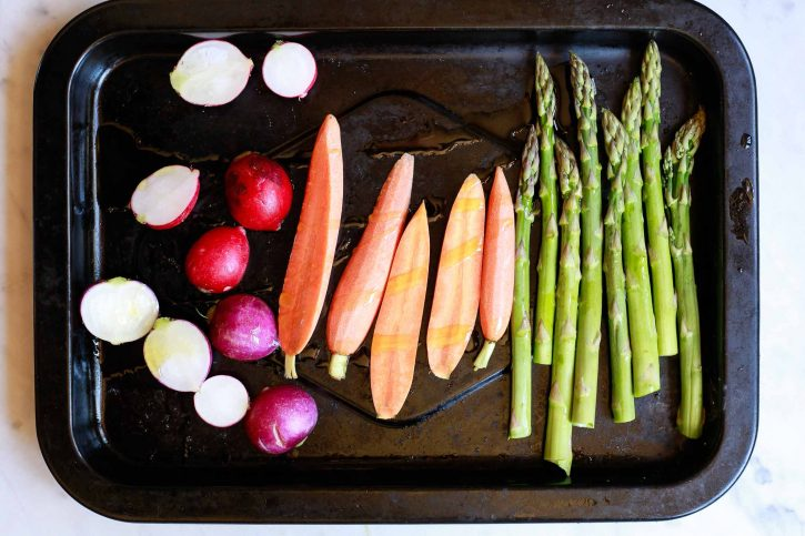 Radish, carrots, and asparagus on a roasting sheet.