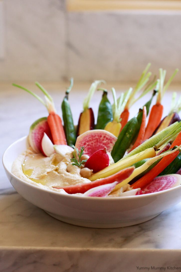 A beautiful bowl of hummus with colorful vegetables.