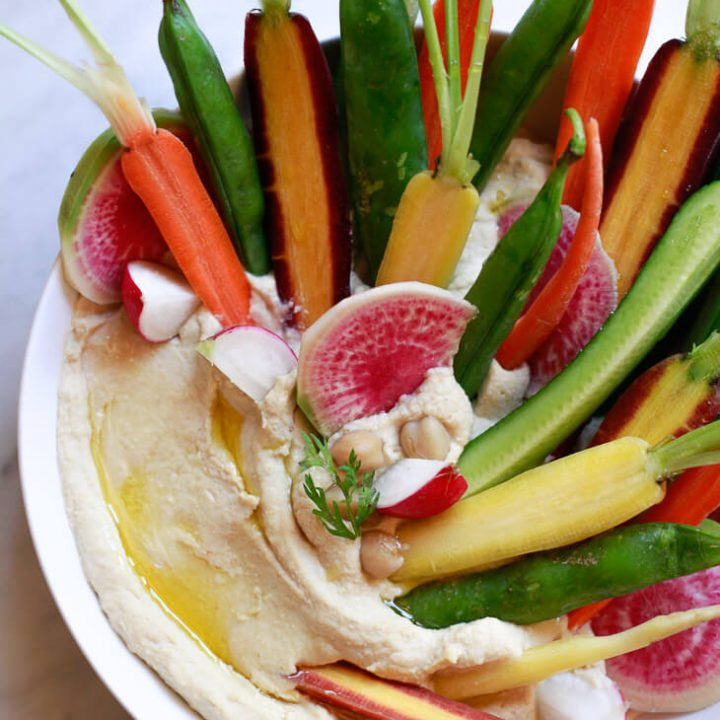 A beautiful bowl of classic homemade hummus topped with colorful carrots, watermelon radish, and cucumber.