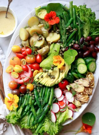 A beautiful white oval platter with vegan colorful Nicoise salad.