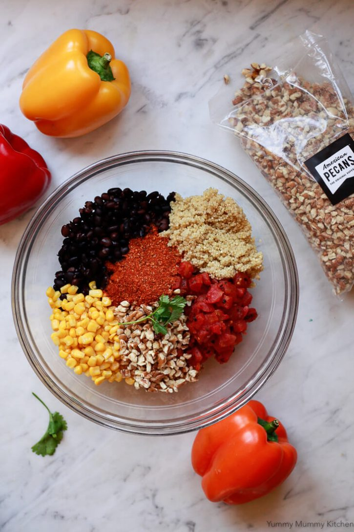 Quinoa, black beans, corn, pecans, taco seasoning, and tomatoes in a glass bowl on a marble countertop. This is the filling ingredients for vegan stuffed bell peppers.