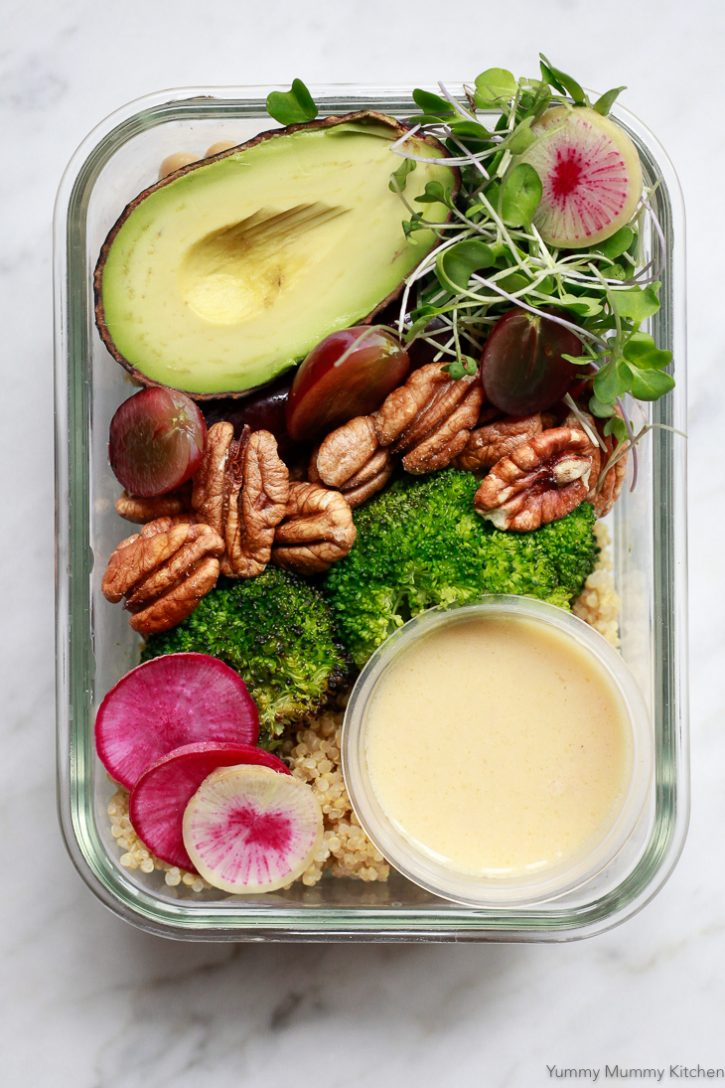 Vegan meal prep lunch or dinner with quinoa, roasted broccoli, pecans, grapes, and avocado. This beautiful meal is in a glass meal prep container with a small container of lemon dressing.