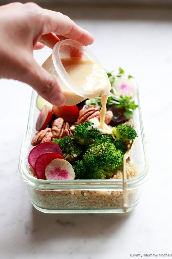 A hand pours homemade lemon vinaigrette salad dressing over a vegan meal prep bowl with quinoa and broccoli.