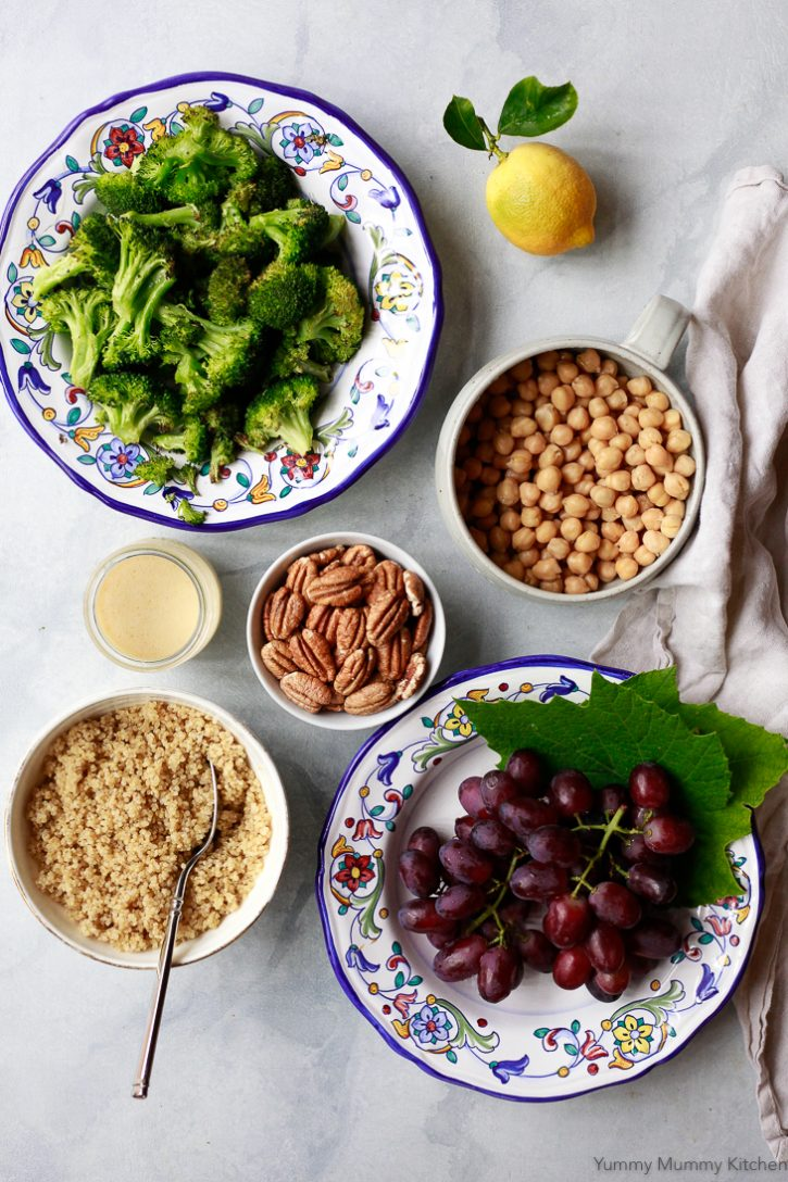 Ingredients for vegan meal prep bowls on a white counter include grapes, quinoa, chickpeas, pecans, broccoli, and lemon vinaigrette dressing.