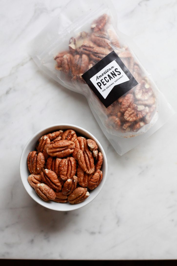 A bag and small bowl of American Pecans sit on a marble kitchen countertop.
