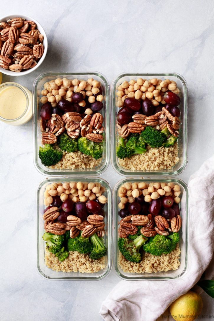 Four glass meal prep containers on a counter filled with quinoa, broccoli, grapes, pecans, and chickpeas. A delicious healthy vegan meal prep idea.