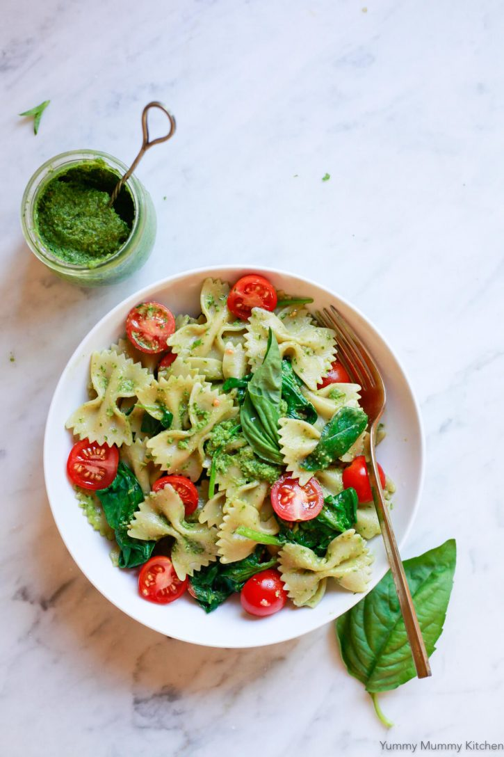A bowl of vegan pesto pasta sits on a white marble countertop with a small jar of pesto sauce on the side.