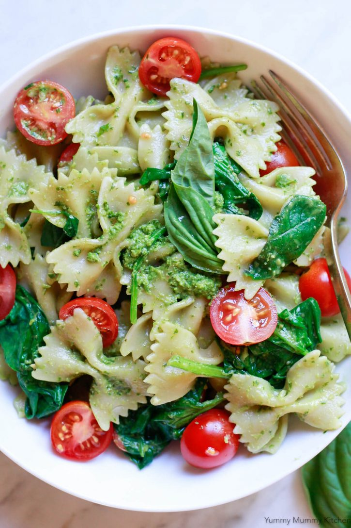 A bowl of vegan pesto pasta made with bowties, cherry tomatoes, spinach and fresh basil pesto.