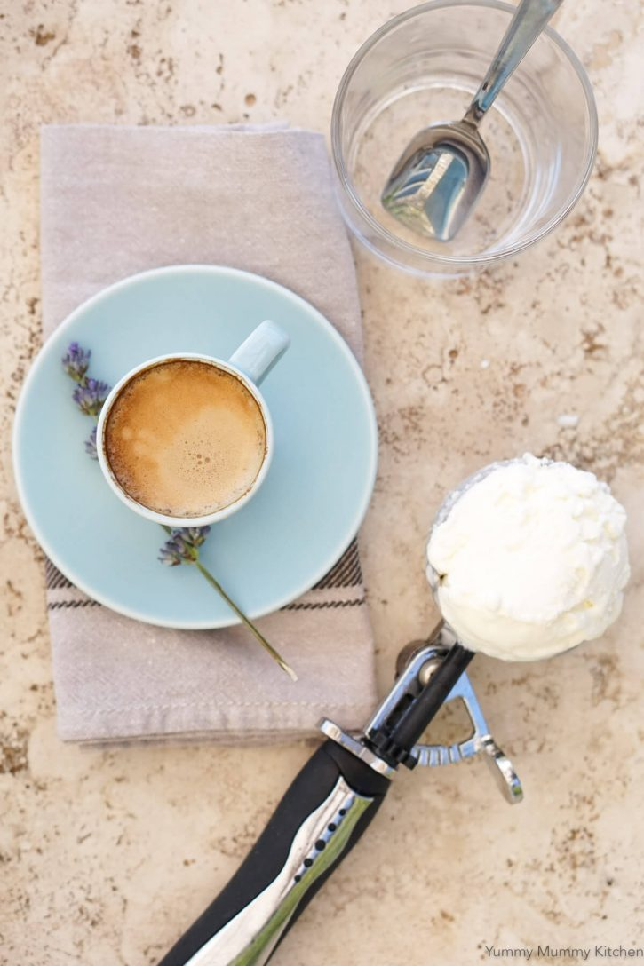 A shot of espresso in a cup, a scoop of vanilla ice cream in an ice cream scooper, and a glass with spoon on a tabletop to make affogato.