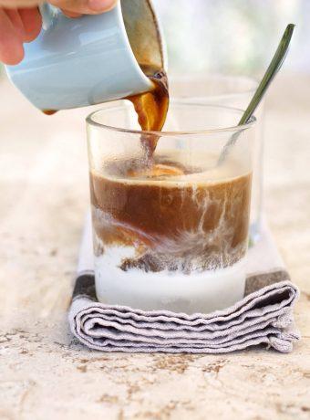 A hand pours a shot of espresso over vanilla ice cream to make affogato, an Italian dessert.