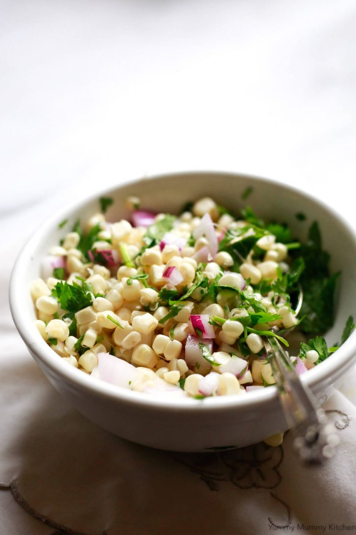 A small white bowl of fresh corn salsa inspired by Chipotle's recipe.